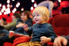 Cute toddler boy watching cartoon movie in the cinema
